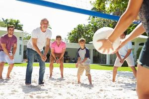 Male Multi Generation Family Playing Volleyball In Garden photo