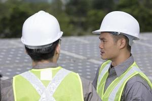 Two Asian engineers in a solar panel station