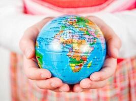 mãos de uma criança segurando o globo