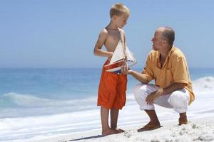 Grandfather and grandson playing with toy boat on sandy beach photo