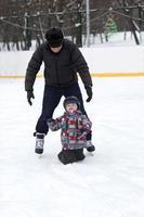 Großvater bringt seinem Enkelkind das Skaten bei