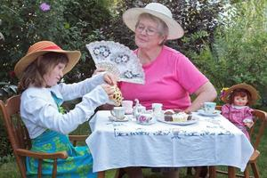 Beautiful little girl and her grandmother having a tea party