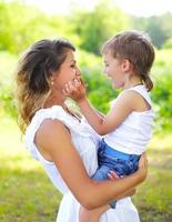 Mother with child son having fun outdoors in summer day