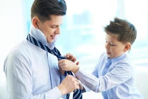 Kid helping his father put on a tie
