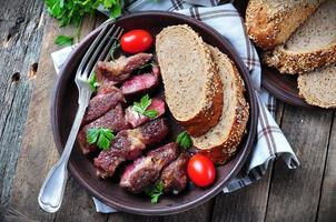 Delicious juicy rare beef steak with rye bread bran
