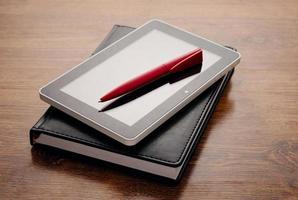 dispositivo de tableta en el cuaderno en la mesa de madera foto