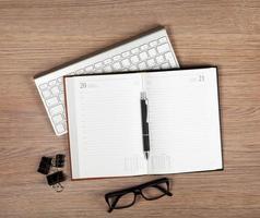 Bloc de notas en blanco con bolígrafo y gafas