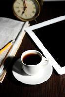 tableta, periódico, taza de café y despertador en la mesa