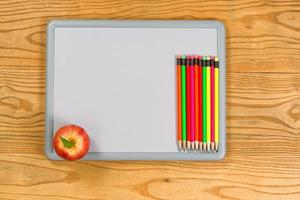 White board with colorful pencils and apple on desktop