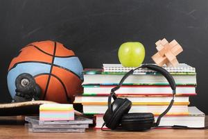 accesorios escolares en escritorio con pizarra en el fondo