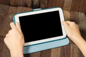 hand holding a tablet on wooden background photo