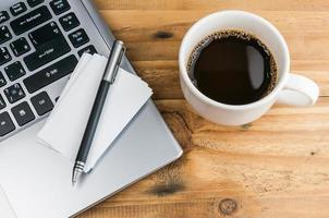 business card and pen over laptop with coffee cup