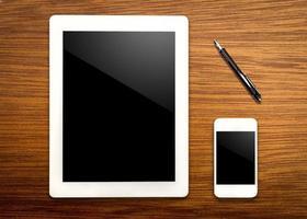 tableta y teléfono inteligente con bolígrafo sobre la mesa foto