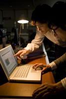 Man facing to PC in dark office photo