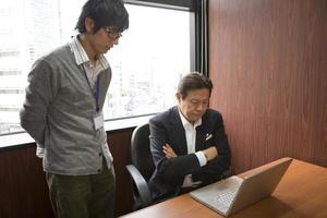 Boss explaining to his staff using PC photo
