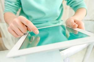 Mano tocando la pantalla en la moderna tableta digital pc. foto