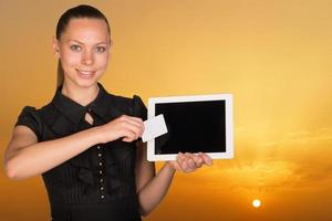 Beautiful businesswoman holding tablet PC and business card in front photo
