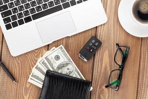 mesa de oficina con pc, taza de café, vasos y dinero en efectivo foto
