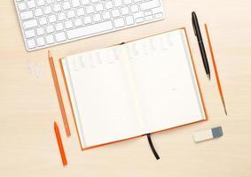 mesa de oficina con bloc de notas en blanco y suministros