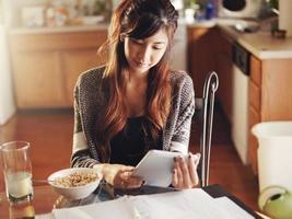 Chica asiática con tableta desayunando