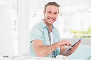 gelukkig casual zakenman met behulp van tablet