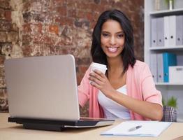 lachende vrouw met koffiekopje en laptop zit aan bureau
