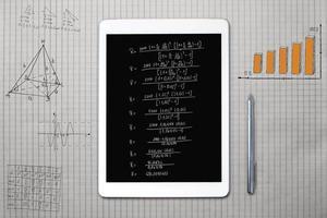 tableta y bocetos matemáticos en una hoja de cuadrado