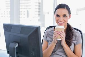 empresária atraente feliz tomando café