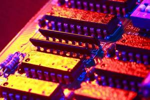 Gold yellow with red light of circuit board with processor close-up photo