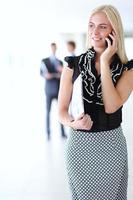 hermosa empresaria mediante teléfono celular, de pie en la oficina