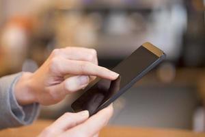 Primer plano de la mano de la mujer usando su teléfono celular en el restaurante foto