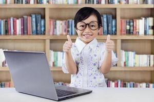 pequeño estudiante satisfecho muestra los pulgares para arriba en la biblioteca foto