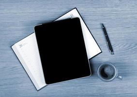 tableta con pantalla en blanco y taza de café