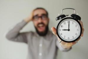 Panic man holds alarm clock and head scared of deadline
