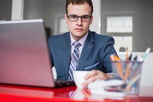 Young businessman working in bright office. photo