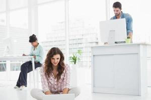Cheerful businesswoman sitting on the floor using laptop