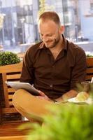 hombre feliz usando tableta al aire libre
