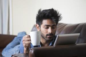 Hombre asiático feliz usando tableta digital en casa en el sofá.