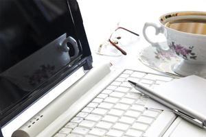 computadora portátil y una taza de café en la oficina