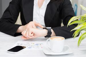 Businesswoman uses smart watch and phone.