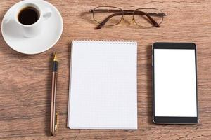 Notebook with pen, smart phone and coffee cup photo