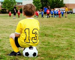Child in uniform watching organized youth soccer photo
