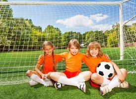 Niños sonrientes sentados en el césped con fútbol foto