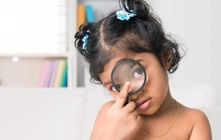niña india mira a la cámara a través de una lupa