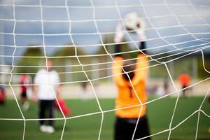 A soccer game with the net in focus as a goalie stops ball