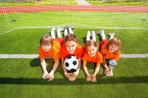 niños sonrientes yacían sobre la hierba con copa dorada foto