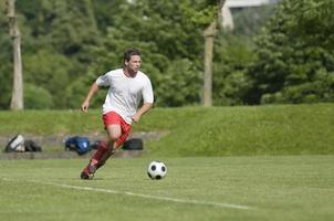 um jogador de futebol masculino driblando a bola pelo campo