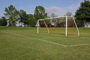An empty soccer goal on a playing field