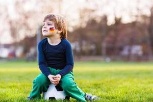 niño rubio de 4 jugando al fútbol con campo de fútbol onl foto