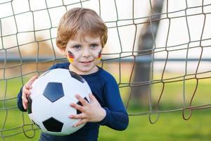 pequeño fanático en la visualización pública de fútbol o fútbol foto